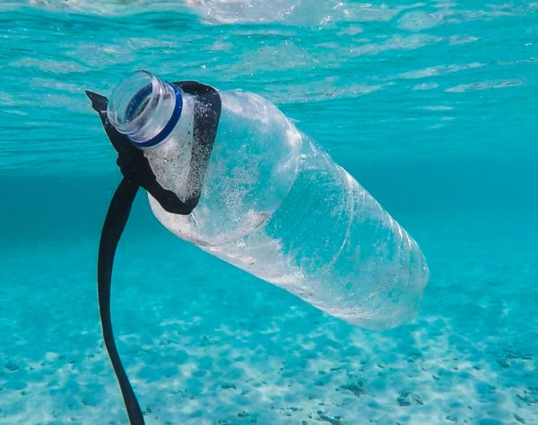The image shows a plastic bottle floating within the ocean.